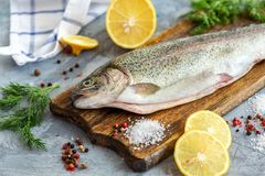 Preparation of rainbow trout. Raw trout, lemon slices, salt pepper and dill on wooden chopping board, selective focus stock images