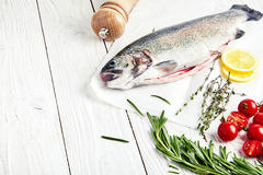 Raw trout, rosemary, tomatoes, lemon, thyme. Raw fresh rainbow trout on baking paper with cherry tomatoes, slices of lemon and sprigs of rosemary and thyme Royalty Free Stock Photos