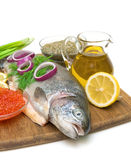 Raw trout, vegetables, olive oil, lemon and red caviar. Raw trout, vegetables, olive oil, lemon, spices and red caviar on white background Royalty Free Stock Images