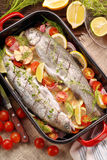 Raw trout with vegetables in a pan ready to bake.  Stock Image