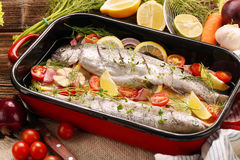 Raw trout with vegetables in a pan ready to bake.  Stock Photo