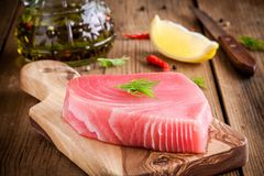 Raw tuna fillet with dill, lemon and olive oil. On rustic background royalty free stock photos