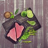 Raw tuna fillet. With salad leaves and limes Stock Photo