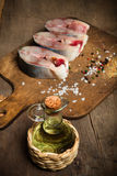 Raw tuna fish and spices for cooking on a old wooden background. Stock Photography