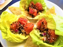 Tuna Poke Boats. Raw Tuna Poke in butter lettuce cups, with black and white sesame seeds and ginger ponzu sauce Stock Images