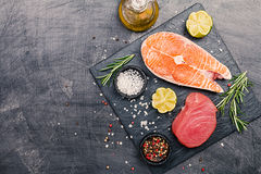 Raw tuna and salmon steak. And ingredients for cooking on a dark background. Top view royalty free stock image