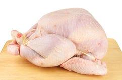 Raw turkey on a board. Raw turkey on a wooden food preparation board stock photography