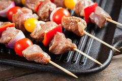 Raw turkey meat skewers with cherry tomatoes, pepper and onion o Stock Image