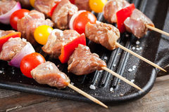 Raw turkey meat skewers with cherry tomatoes, pepper and onion o Stock Photo