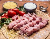 Raw turkey meat on skewers with garlic sauce bulgur seasoned tomatoes and herbs on a cutting board  a wooden background close up Stock Photo