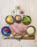 Raw turkey on paper with knife lemon meat onion peas salt pepper on wooden rustic background top view Stock Image