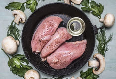 Raw turkey with seasonings and butter on the old cast-iron frying pan with herbs and mushroomsm frame top view close up Stock Photo