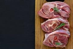 Raw turkey steak meat with bone on wooden board background.  royalty free stock photo