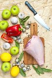 Raw turkey thigh garlic apples lemon red bell pepper quail eggs spices on a wooden board. Top view of a turkey, knife on a beige p. Aper background. Culinary Stock Photos