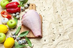 Raw turkey thigh garlic apples lemon red bell pepper quail eggs spices on a wooden board. Top view of a turkey, knife on a beige p. Aper background. Culinary Stock Photo