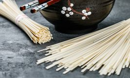 Raw Udon noodles. For cooking Oriental and Asian cuisine on black background. Selective focus Stock Images