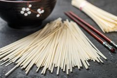 Raw Udon noodles. For cooking Oriental and Asian cuisine on black background. Selective focus Royalty Free Stock Image