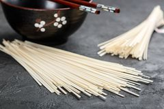 Raw Udon noodles. For cooking Oriental and Asian cuisine on black background. Selective focus Royalty Free Stock Photos