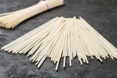 Raw Udon noodles. For cooking Oriental and Asian cuisine on black background. Selective focus Stock Image