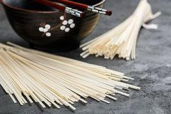 Raw Udon noodles. For cooking Oriental and Asian cuisine on black background. Selective focus Royalty Free Stock Photography