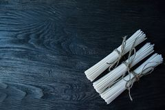 Raw udon noodles in rolls on a dark wooden background. Place for text. View from above stock photos