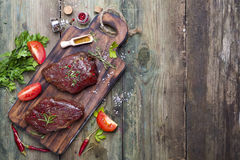 Raw uncooked beef steak meat. With pepper spices and tomato slice on desk on grunge wooden background top view copy space Stock Photos