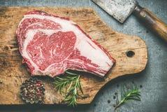 Raw uncooked beef steak rib-eye on board with seasoning