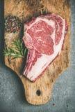 Raw uncooked beef steak rib-eye on board, top view