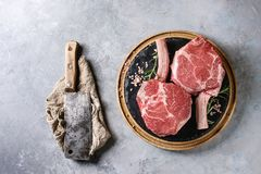 Raw tomahawk steak. Raw uncooked black angus beef tomahawk steaks on bones served with salt, pepper, vintage butcher cleaver on round wooden slate cutting board Royalty Free Stock Photo