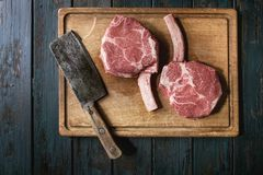Raw tomahawk steak. Raw uncooked black angus beef tomahawk steaks on bones served vintage butcher cleaver on wooden cutting board over dark wooden plank Royalty Free Stock Image