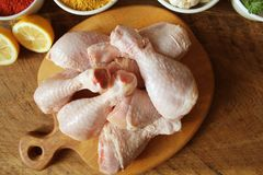 Raw uncooked chicken legs, drumsticks on cutting board, meat with ingredients for cooking. Raw uncooked chicken legs, drumsticks on cuttingn board, meat with Stock Photography