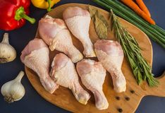 Raw uncooked chicken legs. On wooden board with garlic,carrot,pepper and spice stock photography
