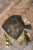 Raw uncooked flatfish on wooden table. Raw uncooked flatfish with lemons, asparagus, herbs, mushrooms and spices on wooden table. European plaice, top view Royalty Free Stock Photo
