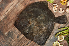 Raw uncooked flatfish on wooden table. Raw uncooked flatfish with lemons, asparagus, herbs, mushrooms and spices on wooden table. European plaice, top view Stock Photos
