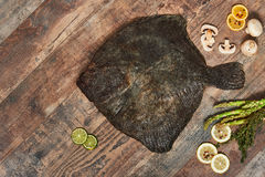 Raw uncooked flatfish on wooden table. Raw uncooked flatfish with lemons, asparagus, herbs, mushrooms and spices on wooden table. European plaice, top view Stock Images