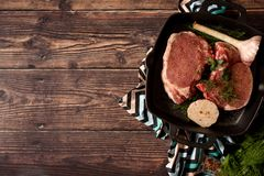 Raw uncooked lamb meat chops with rosemary and garlic in black iron grilling pan, top view, horizontal composition.  royalty free stock photos