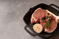 Raw uncooked lamb meat chops with rosemary and garlic in black iron grilling pan, top view, horizontal composition.  stock photography