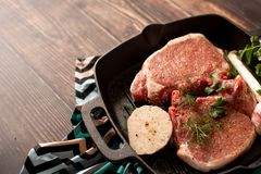 Raw uncooked lamb meat chops with rosemary and garlic in black iron grilling pan, top view, horizontal composition.  royalty free stock photography