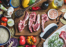 Raw uncooked lamb meat ribs, rice, oil, spices and vegetables. Ingredients for cooking dinner. Raw uncooked lamb meat ribs, rice, oil, spices and vegetables over Royalty Free Stock Images
