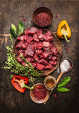 Raw  Uncooked Meat Sliced In Cubes With Fresh Herbs, Vegetables And Spices On Rustic Wooden Background, Ingredients For Beef Stew