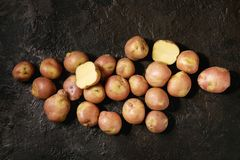 Raw potatoes miss blush. Raw uncooked organic potatoes named miss blush, whole and slice over dark texture background. Top view, copy space Royalty Free Stock Images