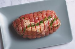 Raw Uncooked Pork, Rolled Meat with Herbs and Seasoning. On Grey Background Royalty Free Stock Images