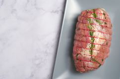 Raw Uncooked Pork, Rolled Meat with Herbs and Seasoning. On Grey Background Royalty Free Stock Photos