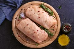 Raw uncooked poultry meat cut on wooden tray. Duck breasts with honey, rosemary and spices. Raw uncooked poultry meat cut on wooden tray. Duck breasts with royalty free stock image