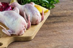 Raw uncooked quail meat. Ingredients for cooking healthy meat dinner. Raw uncooked quail meat with vegetables. Selective focus. copy space Royalty Free Stock Photography