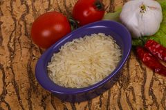 Raw uncooked rice in the bowl. Served pepper and salad leaves stock photography