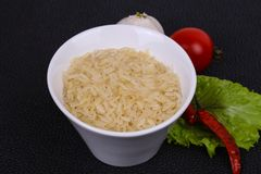 Raw uncooked rice in the bowl. Served pepper and salad leaves stock photo
