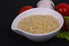 Raw uncooked rice in the bowl. Served pepper and salad leaves royalty free stock photos