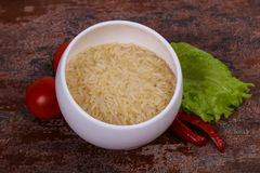 Raw uncooked rice in the bowl. Served pepper and salad leaves royalty free stock photo