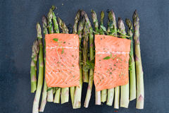 Raw uncooked salmon and asparagus on baking tray. Two pieces of fillet of raw uncooked salmon on green asparagus on baking tray garnished with fresh thyme royalty free stock image